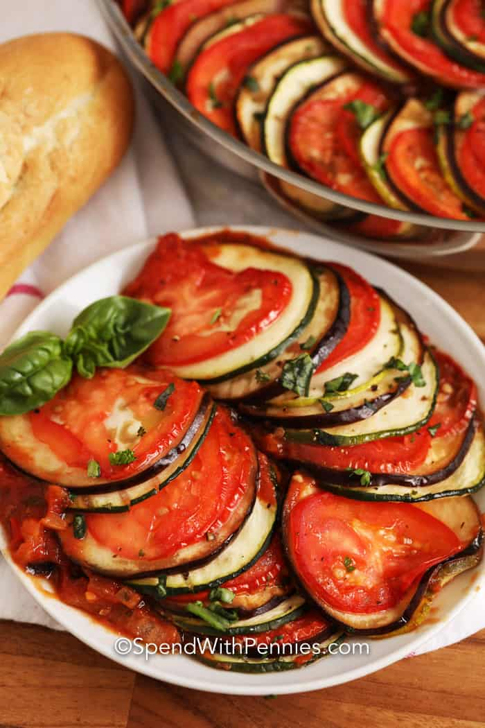 Ratatouille on a white plate with basil and a loaf of bread