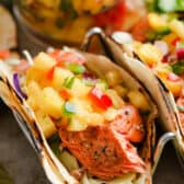 Salmon Tacos with Pineapple Salsa closeup of taco with salsa behind