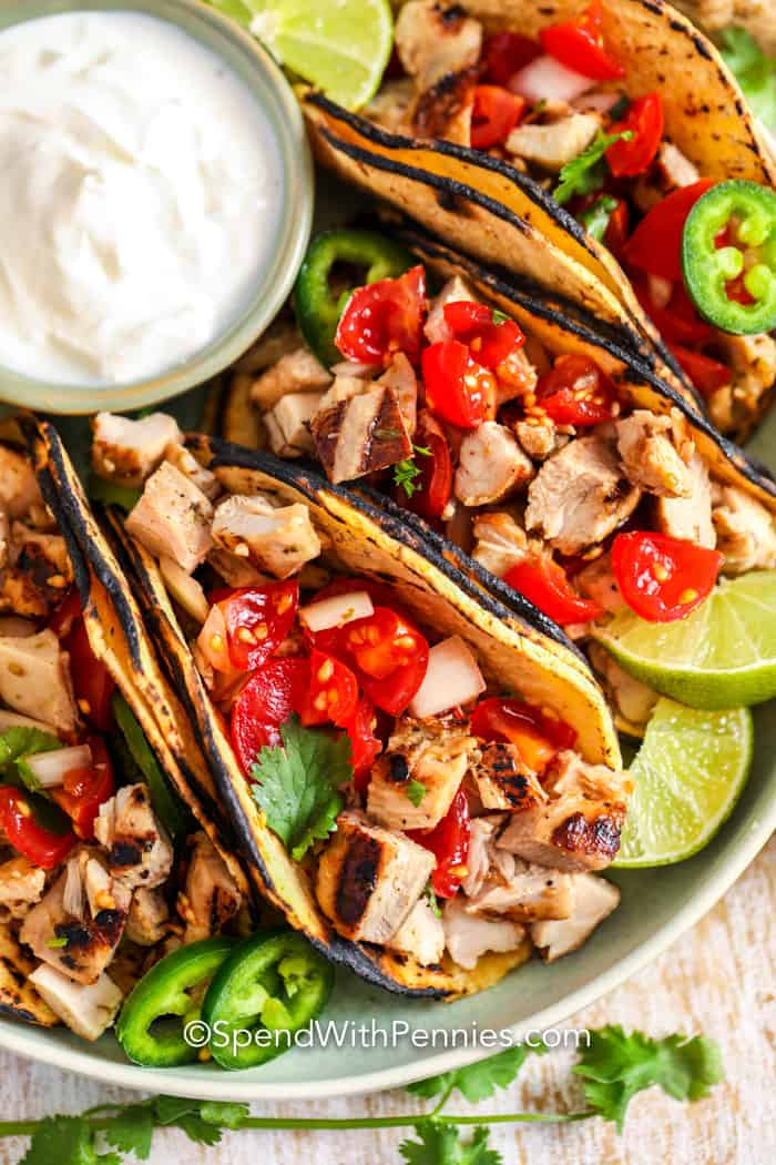Street tacos on a plate with sour cream and limes