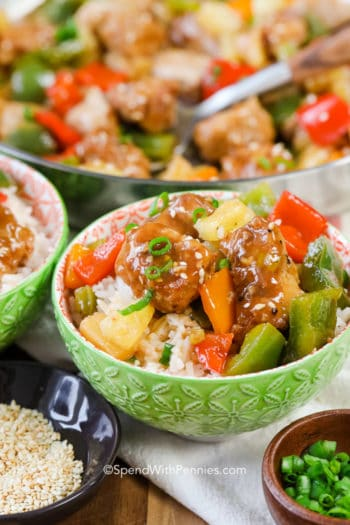Sweet and sour pork in a green bowl with green onions