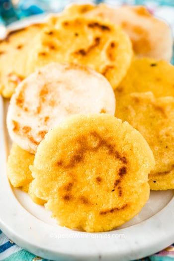 Yellow and white arepas on a serving dish.