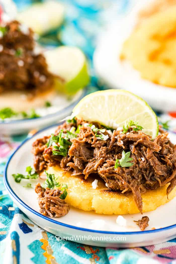 Arepas topped with barbacoa beef.