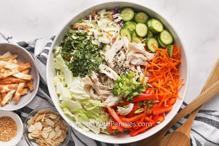 Asian Chicken Salad with ingredients in smaller bowls beside and wooden spoons