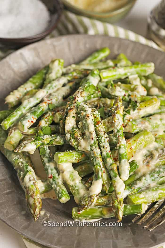 A close up of creamy asparagus topped with parmesan cheese in a serving dish.
