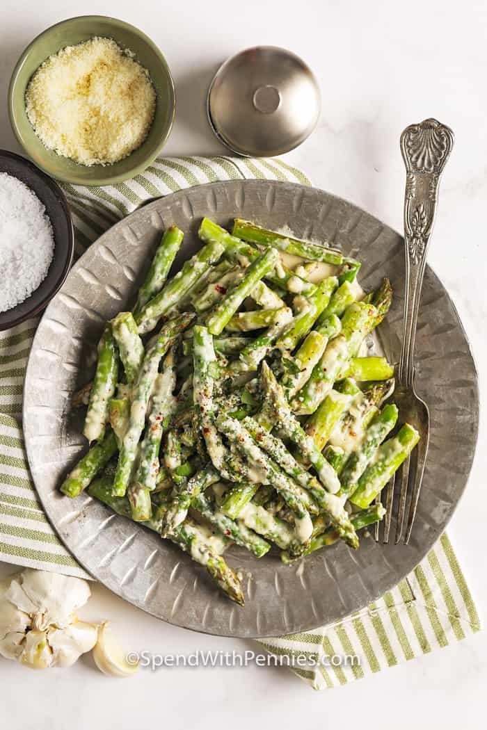 A serving dish of creamy asparagus topped with parmesan cheese.