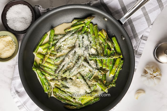Creamy asparagus being prepared in a frying pan.