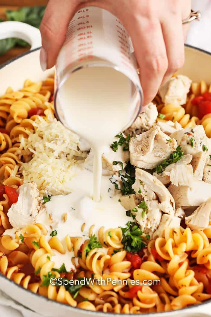 Cream being poured over other ingredients for Creamy Tomato Chicken Pasta Skillet.