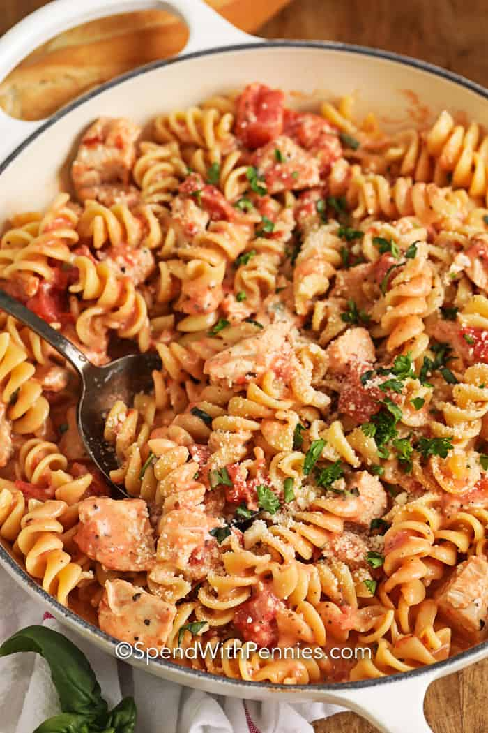 Overhead image of Creamy Tomato Chicken Pasta Skillet in a pot with a spoon.