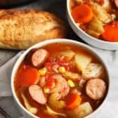 Two bowls of crockpot potato and sausage soup.