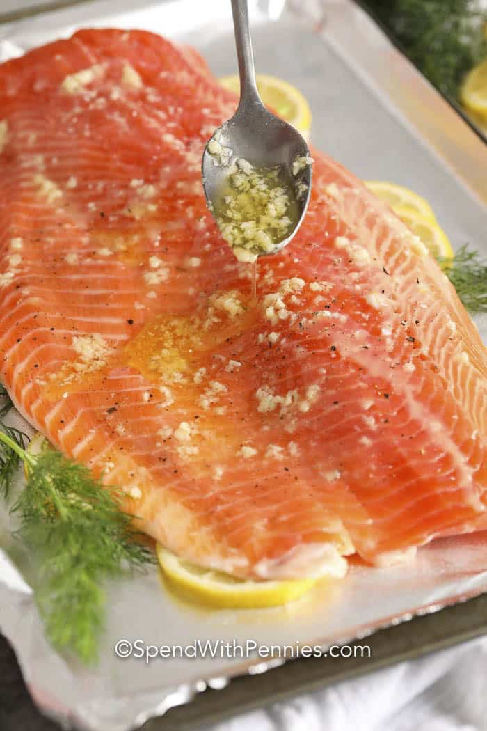 Salmon fillet being topped with garlic butter.