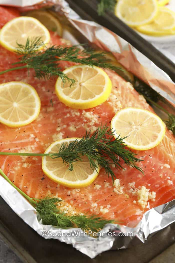 Raw Salmon fillet topped with garlic butter, lemon slices, and dill.