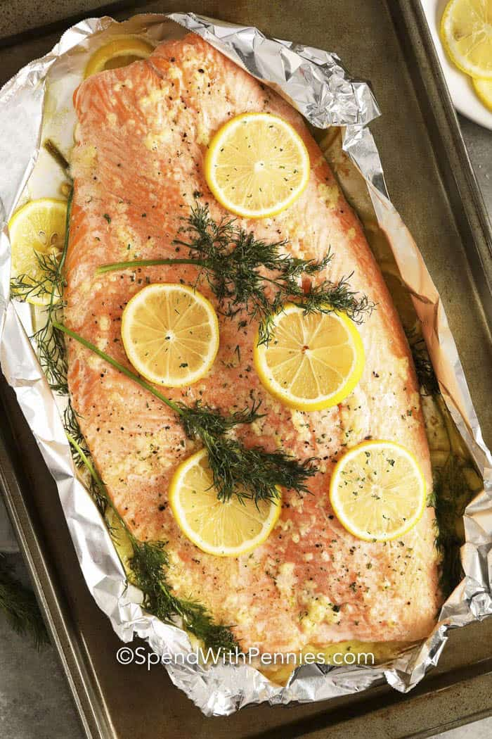 Baked Salmon on foil with lemon slices and dill.