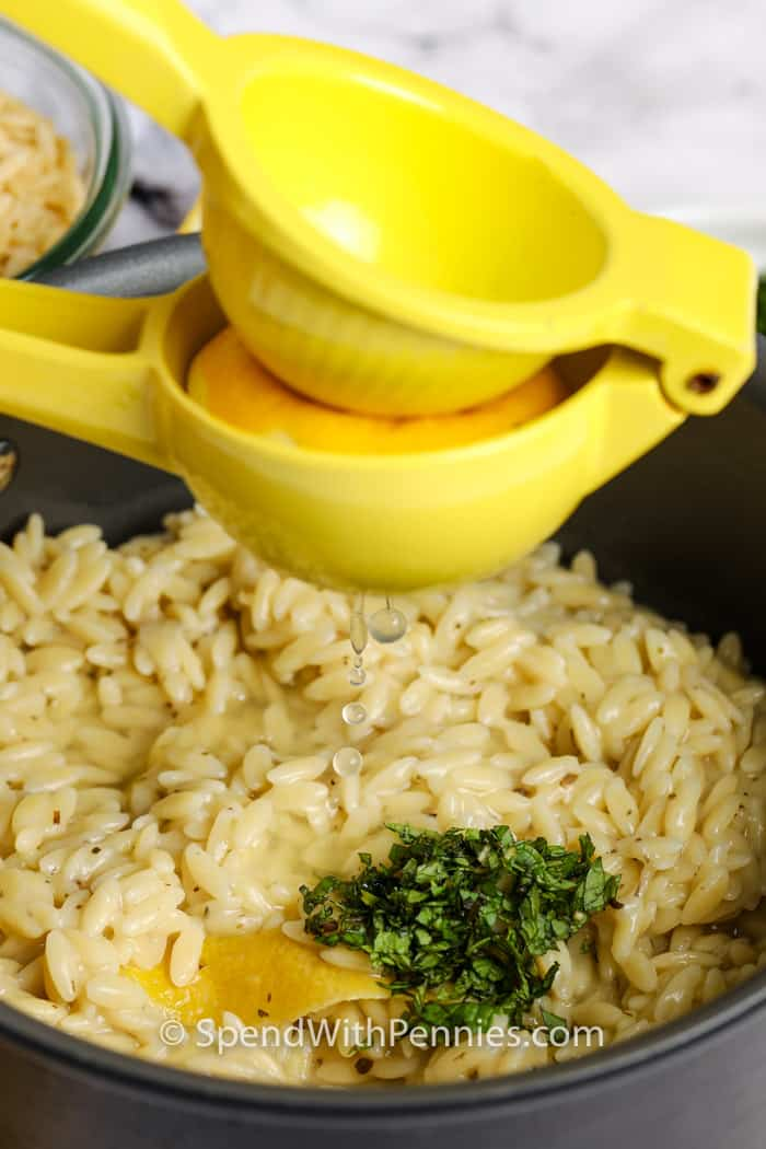 Orzo in a pot with some mint garnish on top, with lemon juice being squeezed into the pot.