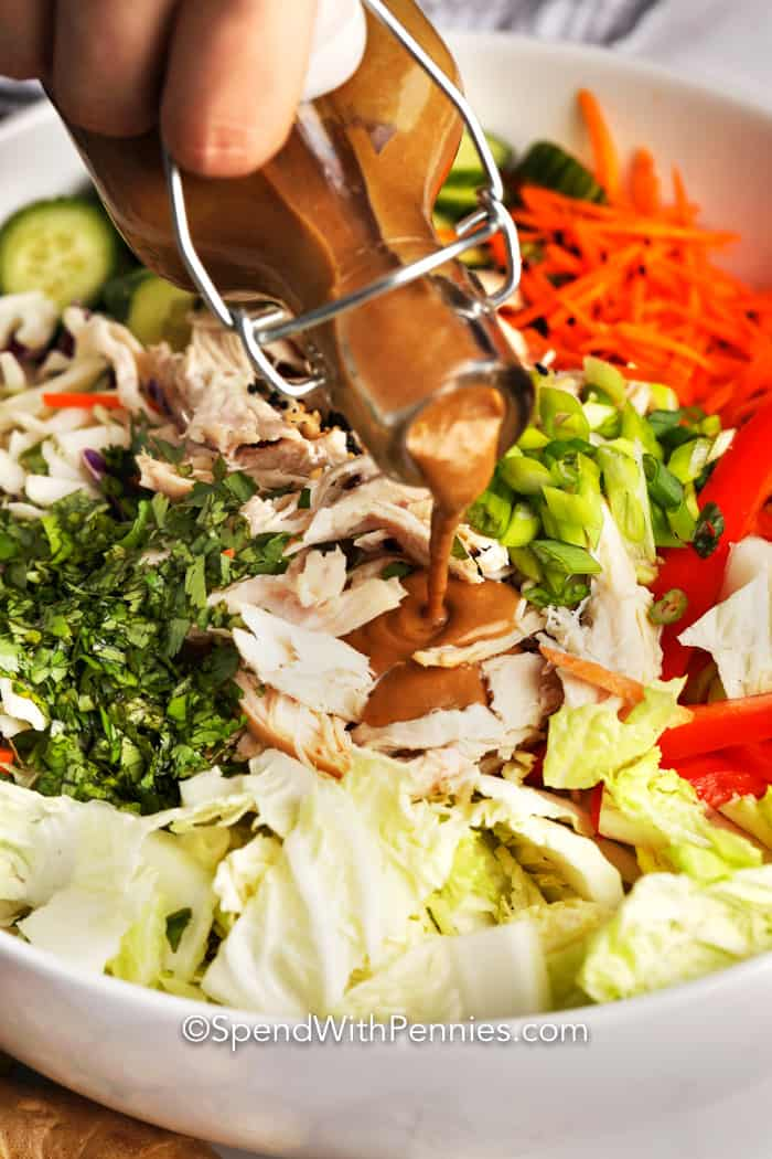 Image of Peanut Dressing in a jar being poured over a salad.