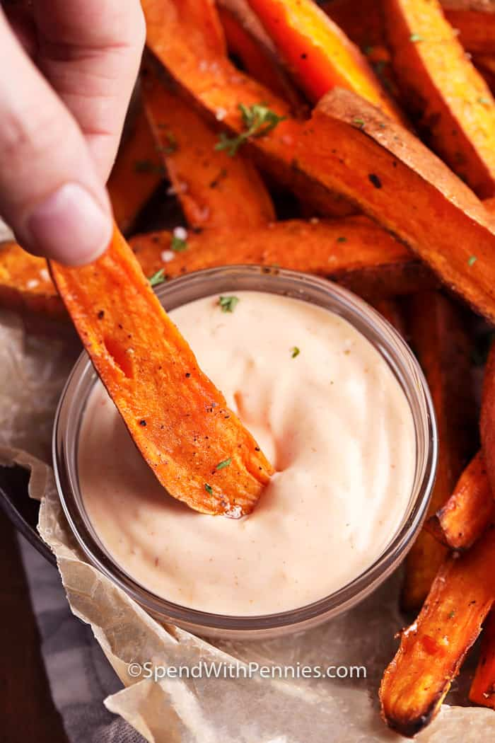 Sweet potato fries being dipped in aioli