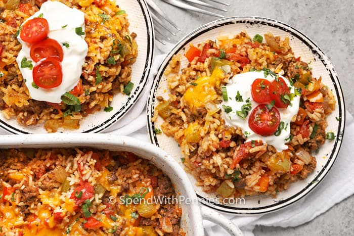Two plates of stuffed pepper casserole, both garnished with sour cream and tomatoes.