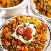 Taco Stuffed Pepper Casserole in a dish with tomatoes and sour cream on top