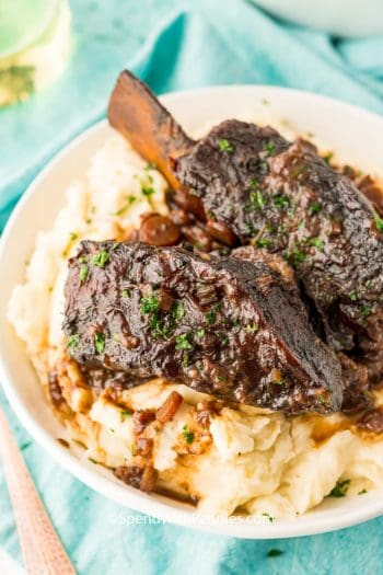 beef shot ribs on mashed potatoes in a white bowl.