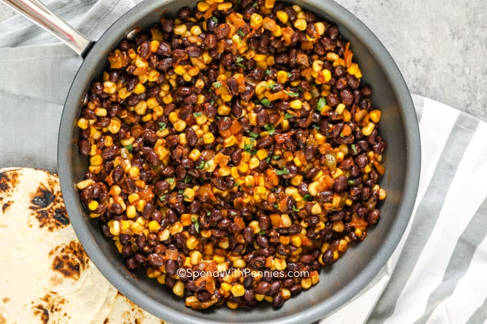 Black Beans, corn and seasonings in a frying pan with taco shells