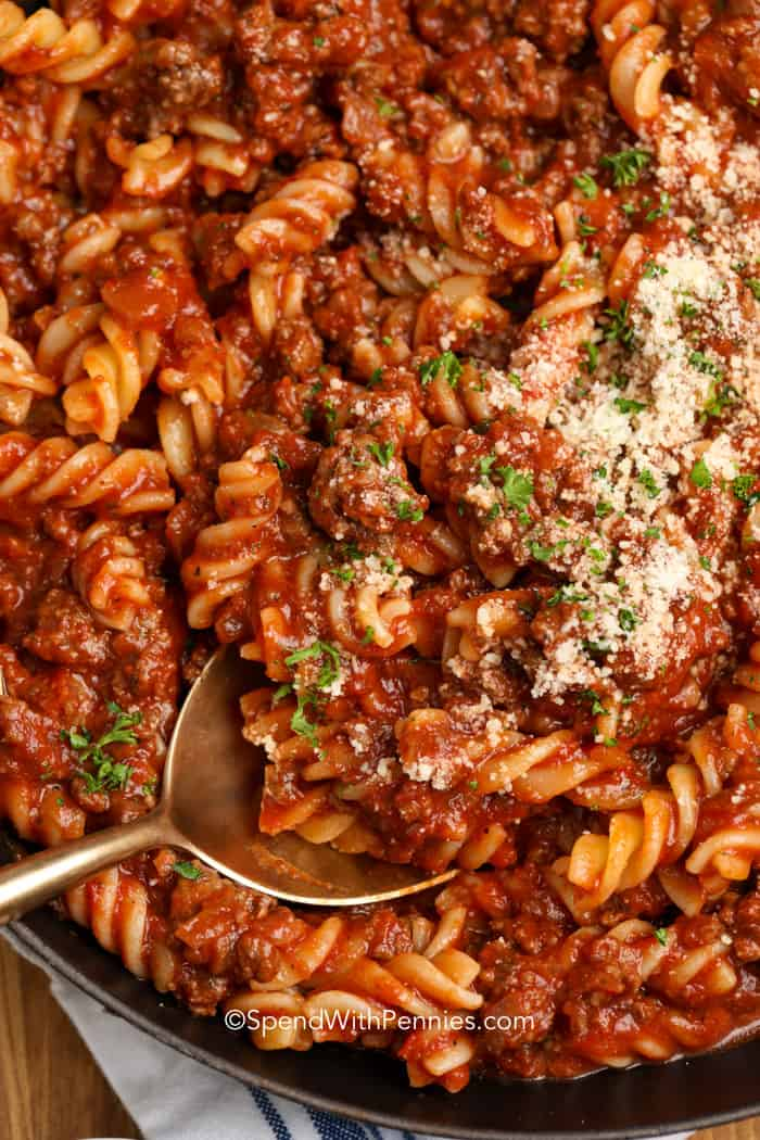 fusilli with meat sauce and parmesan cheese being served with a spoon