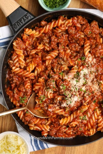 Fusilli with meat sauce in a pan garnished with parsley.
