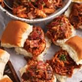 BBQ chicken sliders on parchment paper with the bowl of meat on the side