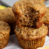 Banana Bread Muffins stacked on parchment paper with bananas