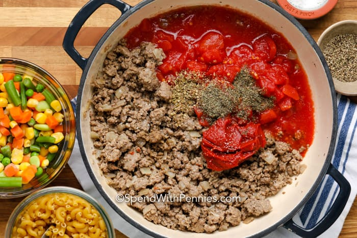 Ground beef, tomatoes, tomato paste, and seasoning in a soup pot with remaining ingredients in bowls around it.
