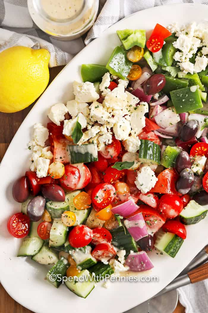 Greek salad on a serving platter with dressing beside it.