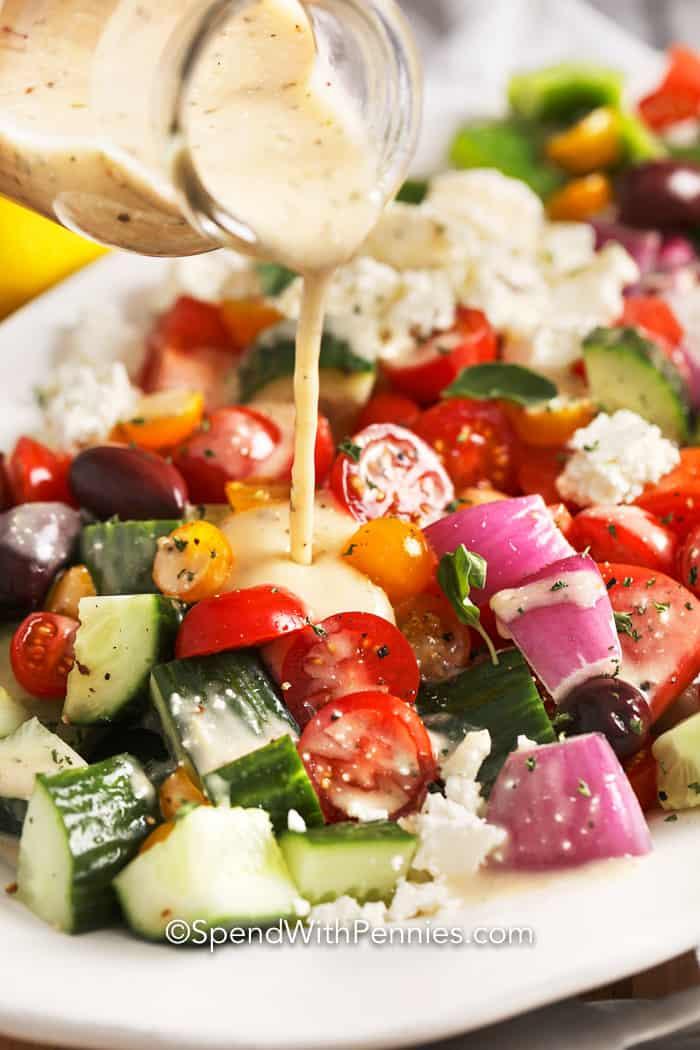 Greek dressing being poured over salad.