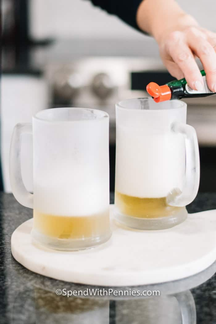 Food colouring being poured into two mugs