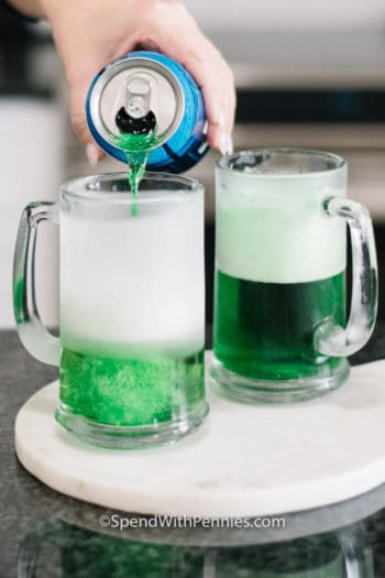 Mugs with green beer on a marble board with a can of beer being poured in
