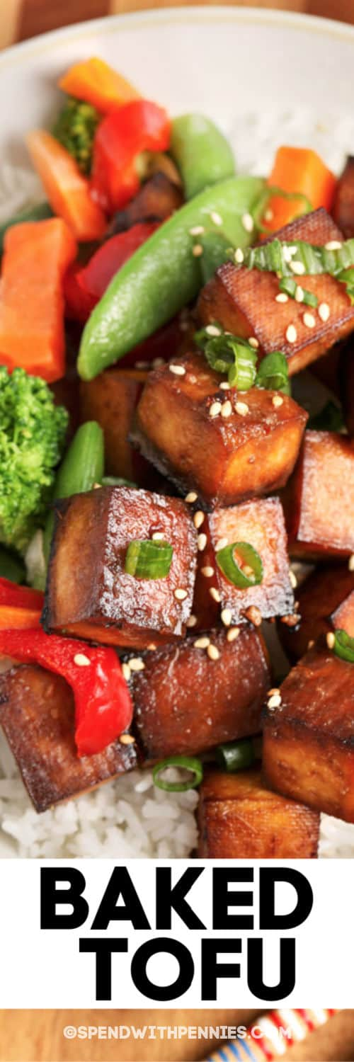 Close up of a serving of baked tofu garnished with sesame seeds with writing