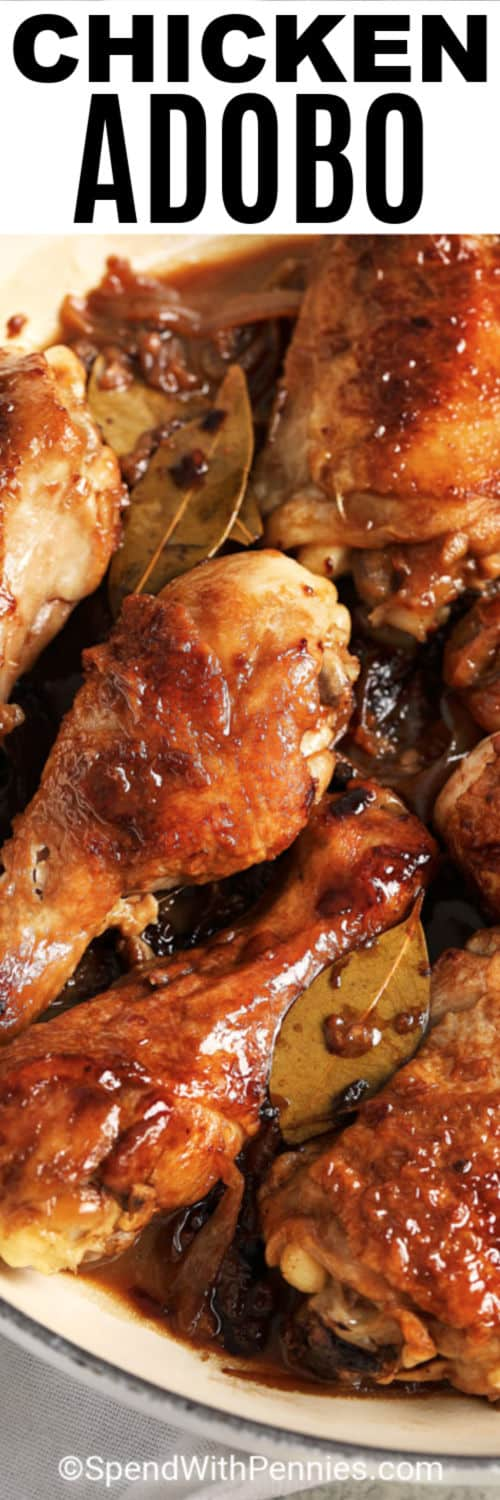 Close up of chicken adobo with bay leaves and writing on top.