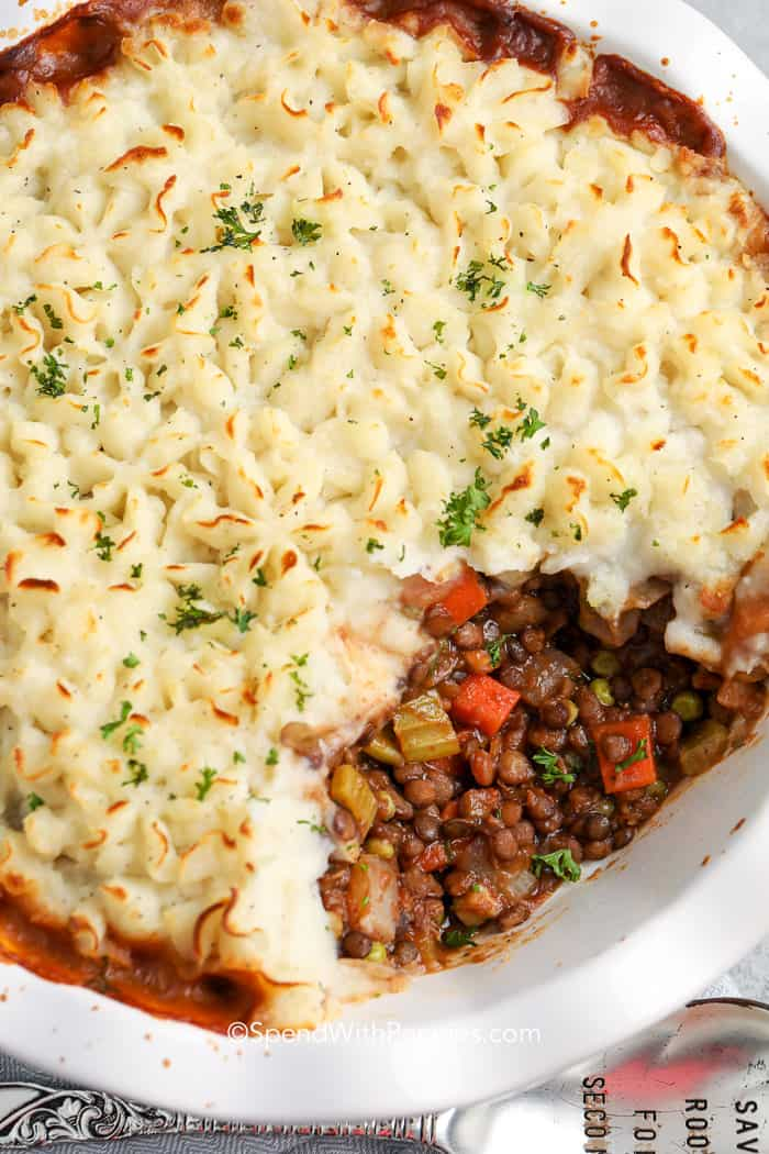 lentil shepherds pie in a white pie plate with a scoop taken out