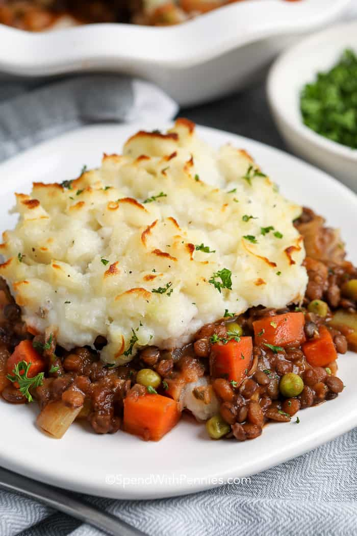 A plate of lentil shepherd's pie topped with mashed potatoes and parsley