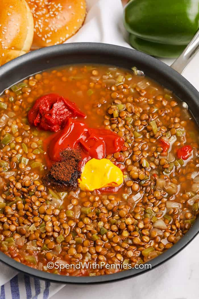 Lentils topped with remaining mixture ingredients in a frying pan.