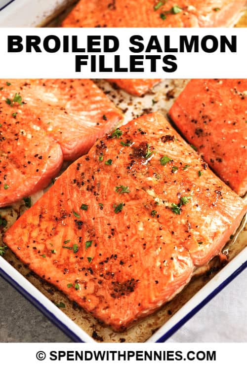 Four broiled salmon fillets in a baking dish, garnished with parsley with text.