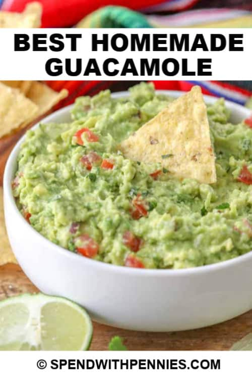 A bowl of the best homemade guacamole served with lime and chips with writing.