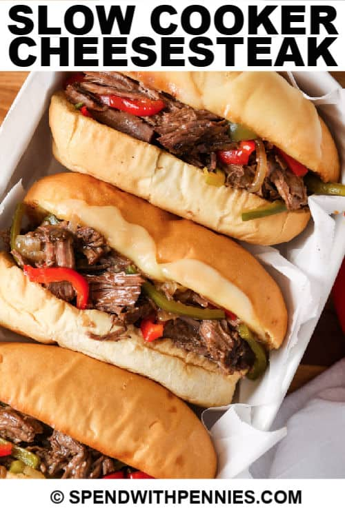 Three prepared cheesesteaks in a tray with writing