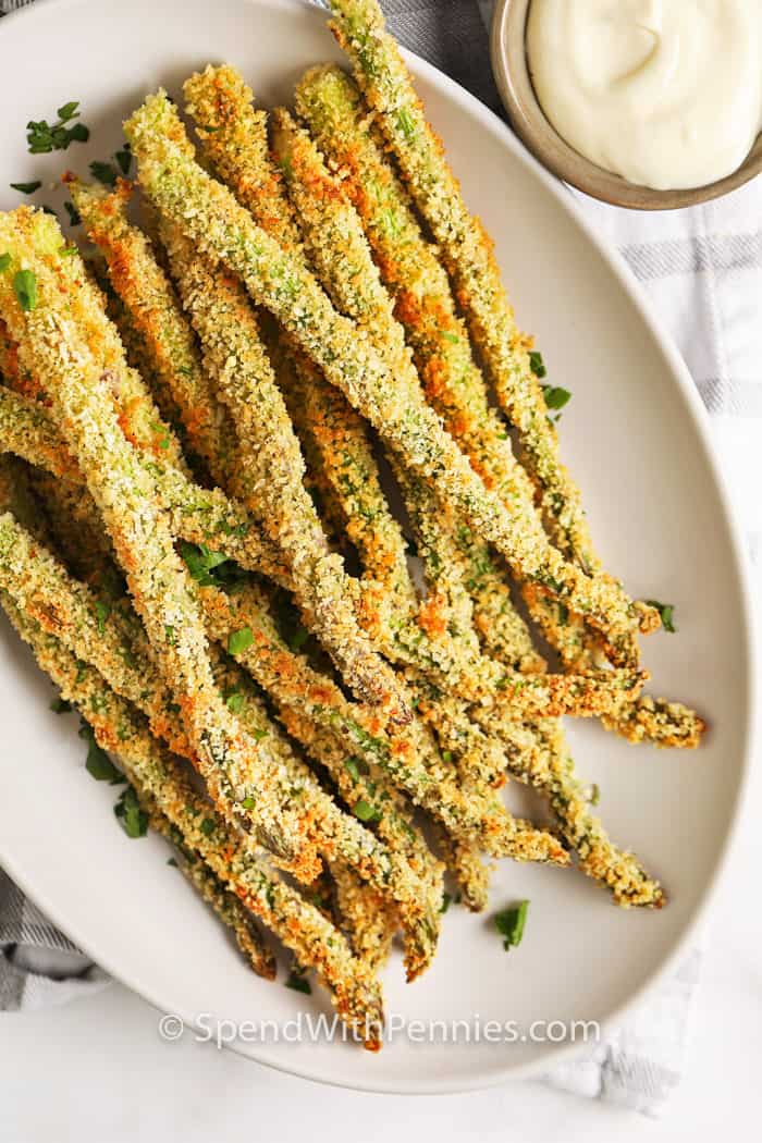 Breaded asparagus fries on a plate with aioli in a bowl