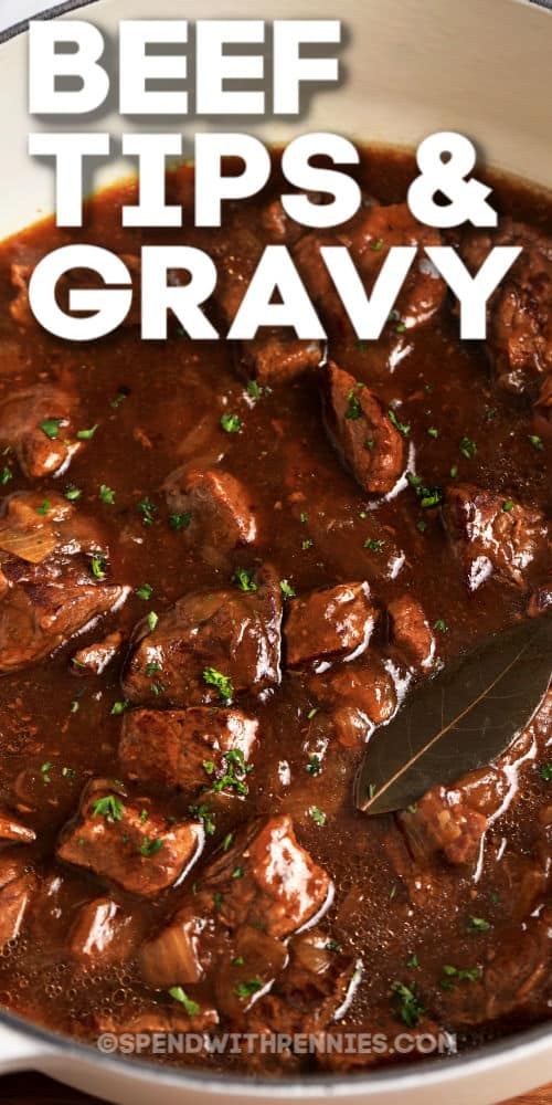 Beef tips and gravy in a pot with a bay leaf, garnished with parsley with writing.