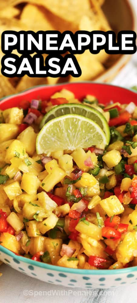 Pineapple salsa topped with lime wedges and cilantro with writing