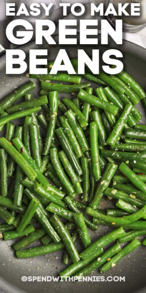 Green beans being sauteed in a pan with writing