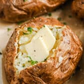 close up of Air Fryer Baked Potatoes cut open with butter and seasoning