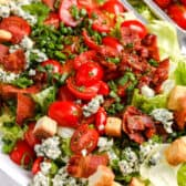a BLT salad over fresh lettuce with croutons and herbs