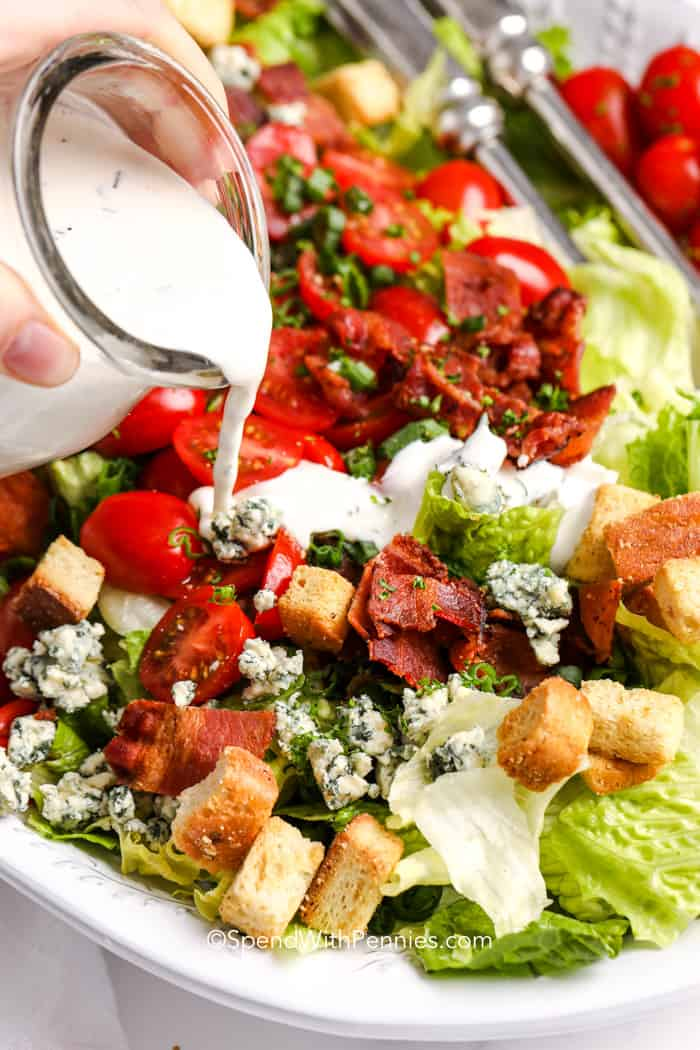dressing being poured over a BLT salad.