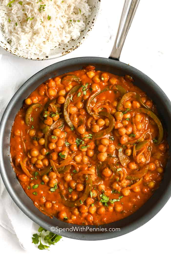 Curried Chickpeas in a skillet with a bowl of rice