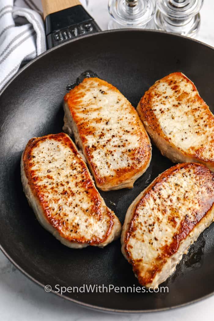 pork chops frying in a pan