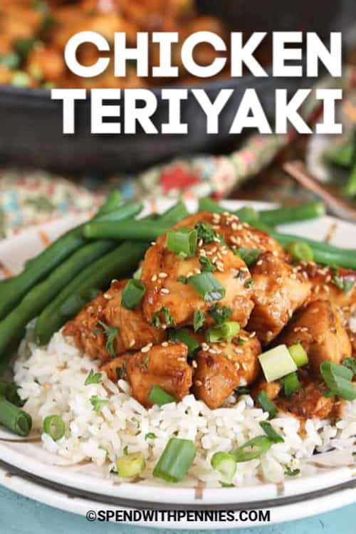 Teriyaki Chicken sprinkled with sesame seeds and green onions, white rice and green beans served on a white plate.